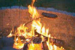 Saucisses de torréfaction sur le feu de camp Images stock