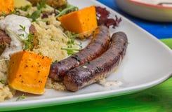 Saucisses de Turkisk avec le quinoa et le potiron rôti Photos stock