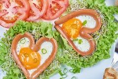 Saucisses en forme de coeur avec des oeufs au plat Image libre de droits