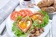 Saucisses en forme de coeur avec des oeufs au plat Images libres de droits