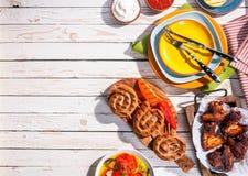 Saucisses et ailes de poulet grillées sur le Tableau de pique-nique Photo libre de droits