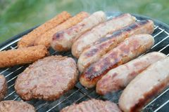 Saucisses et hamburgers sur le barbecue Photos stock