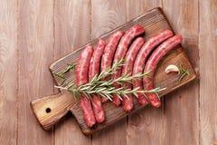 Saucisses et ingrédients crus pour la cuisson Photographie stock libre de droits