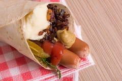 Saucisses et mâche dans un cône de pain plat Photographie stock libre de droits