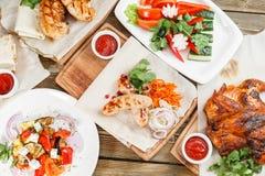 Saucisses et poulet grillés Servir sur un conseil en bois sur une table rustique Menu de rôtisserie, une série de photos Photos libres de droits