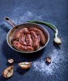 Saucisses four-cuites au four savoureuses dans une poêle sur un fond foncé Photos stock