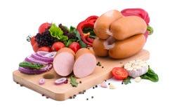 Saucisses fraîches, laitue, poivron rouge et tomates sur un conseil en bois Composition en viande sur un fond blanc Photos libres de droits