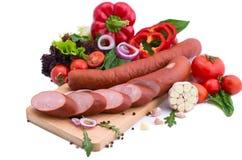 Saucisses fraîches, laitue, poivron rouge et tomates sur un conseil en bois Composition en viande sur un fond blanc Images stock