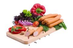 Saucisses fraîches, laitue, poivron rouge et tomates sur un conseil en bois Composition en viande sur un fond blanc Images libres de droits