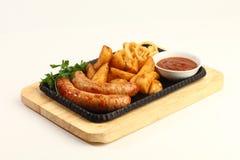Saucisses frites avec les pommes de terre frites Servi sur un conseil en bois avec la sauce tomate Image horizontale Image stock