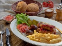 Saucisses frites avec les pommes frites, la salade et les champignons image libre de droits
