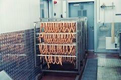 Saucisses fumées à l'usine de traitement des denrées alimentaires des produits alimentaires, modifiée la tonalité photo stock