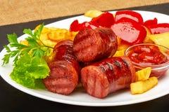 Saucisses grillées avec les fritures de pommes de terre et le ketchup de poivron et rouge bulgare doux de sauce Photographie stock