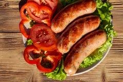 Saucisses grillées avec les légumes frais sur la table en bois photos stock
