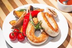 Saucisses grillées avec les pommes de terre, les tomates-cerises et les herbes cuites au four photographie stock