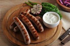 Saucisses grillées de bratwurst avec de la sauce, les épinards et l'ail Photo libre de droits