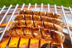 Saucisses grillées en plan rapproché sur la grille images stock