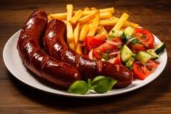 Saucisses grillées, frites et salade végétale Photo stock
