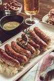 Saucisses grillées par Allemand avec la salade de choux, la moutarde et la bière Images libres de droits