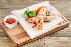 Saucisses grillées Servir sur un conseil en bois sur une table rustique Menu de rôtisserie, une série de photos de différent Photographie stock libre de droits