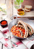 Saucisses grillées avec des haricots en sauce tomate Photographie stock