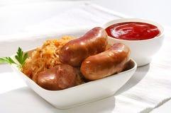 saucisses, pommes de terre et choucroute grillées sur faire cuire la casserole, sur le fond blanc Photos libres de droits