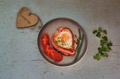 Saucisses sous la forme des coeurs, oeufs brouillés et persil, de plat de couleur Images libres de droits