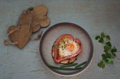 Saucisses sous la forme des coeurs, oeufs brouillés et persil, de plat de couleur Photo libre de droits