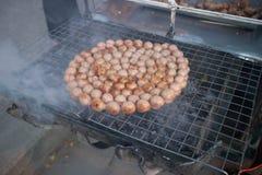 Saucisses thaïlandaises grillées sur le fourneau sur à coté la rue Images stock