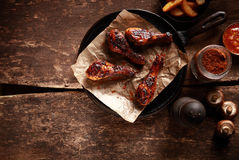 Saucy Barbecued Chicken Drumsticks on Iron Pan Stock Image