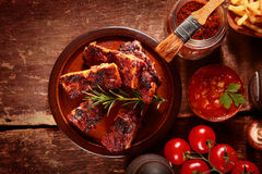 Saucy Barbecued Spareribs with Various Ingredients. High Angle Looking Down at Saucy Barbecued Spareribs Surrounded by Various Ingredients Royalty Free Stock Photo