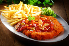 Saucy Crumbled Zigeunerschnitzel with Fries on Plate Royalty Free Stock Photos