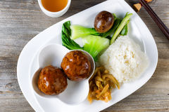 Saucy meatball dish in white plate ready to eat. High angled view of Asian saucy meatballs, rice, egg, cucumber and bok choy on white plate. Chopsticks and green Stock Photos