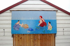 Saucy postcard beach hut painting. Photo of a saucy postcard painting on beach hut typical of british 1960/70's postcards sent from holiday destinations Royalty Free Stock Images