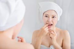 Saudável branco de fio dental do uso da mulher com o espelho no banheiro fotografia de stock royalty free
