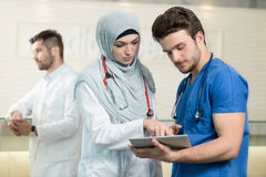 Saudi arab doctors working with a tablet. Saudi arab doctors working with a tablet Stock Photography