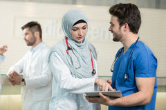 Saudi arab doctors working with a tablet. Saudi arab doctors working with a tablet Royalty Free Stock Images