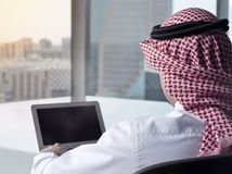 Saudi Arab Man Watching Laptop at Work Contemplating stock photography