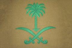 Saudi Arabia coat of arms. Embroidery of Saudi Arabia coat of arms on gray fabric stock photography