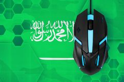 Saudi Arabia flag and computer mouse. Concept of country representing e-sports team. Saudi Arabia flag and modern backlit computer mouse. Concept of country stock image