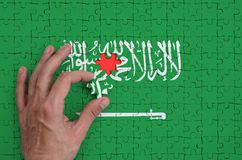 Saudi Arabia flag is depicted on a puzzle, which the man`s hand completes to fold.  royalty free stock photography