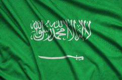 Saudi Arabia flag is depicted on a sports cloth fabric with many folds. Sport team banner. Saudi Arabia flag is depicted on a sports cloth fabric with many folds stock photos