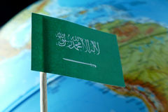 Saudi Arabia flag with a globe map as a background Stock Images