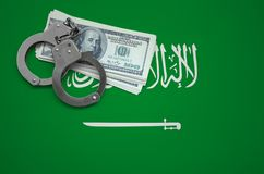 Saudi Arabia flag with handcuffs and a bundle of dollars. The concept of breaking the law and thieves crimes.  royalty free stock photography