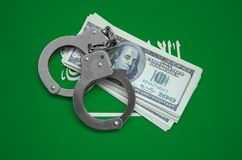 Saudi Arabia flag with handcuffs and a bundle of dollars. Currency corruption in the country. Financial crimes.  stock image