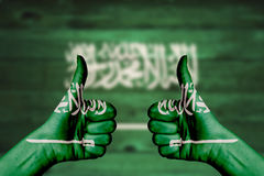 Saudi Arabia flag painted on female hands thumbs up. With blurry wooden background royalty free stock images