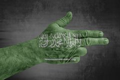 Saudi Arabia flag painted on male hand like a gun. Close royalty free stock image