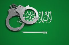 Saudi Arabia flag and police handcuffs. The concept of crime and offenses in the country.  royalty free stock image