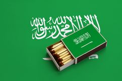 Saudi Arabia flag is shown in an open matchbox, which is filled with matches and lies on a large flag.  stock photo