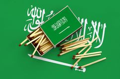 Saudi Arabia flag is shown on an open matchbox, from which several matches fall and lies on a large flag.  stock images